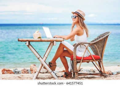 Young sexy woman with beautiful legs sitting at the table on ocean background, using laptop with empty white screen on the beach. Girl Freelancer remote working. digital nomad