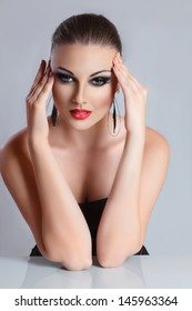 Young sexy woman with beautiful makeup studio portrait against neutral light gray background