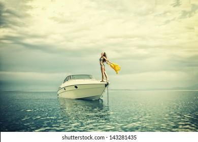 Young sexy woman in bikini enjoying  her private yacht