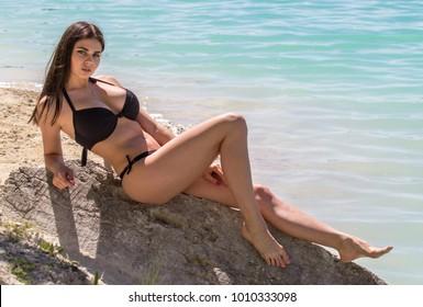 Young sexy woman in a black bikini on sea background