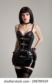 Young sexy woman in black fetish corset, mini skirt, and stockings
