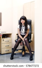 Young sexy woman in black stockings sitting on workplace in the office