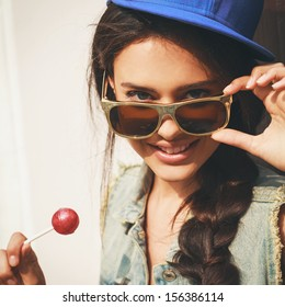 Young sexy woman in blue cap and jeans jacket  looking at camera  through sunglasses .  Outdoors, lifestyle.