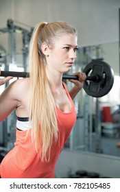 Young sexy woman is doing her sport fitnes workout in the gym. sit up, barbell, dumbbell, stretching and a brake to drink some water