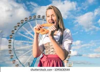 young sexy woman is doing oktoberfest spring summer folk festival in munic. She is wearing a dirndl and holding a heart bretzel in her hand. curly ferris wheel