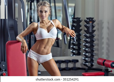 Young sexy woman dressed in white clothes in the gym and looking at camera