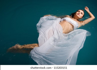 Young sexy woman floating on swimming pool in white dress. beauty shot