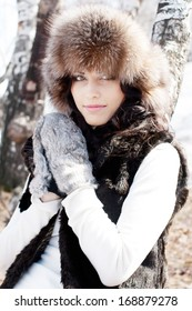 Young sexy woman in a fur hat and mittens in the early spring