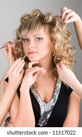 Young sexy woman getting a make-up by many hands