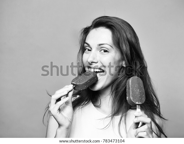 young sexy woman or girl with long brunette hair and pretty smiling happy face eating chocolate ice lolly in white shirt in studio on grey background, copy space