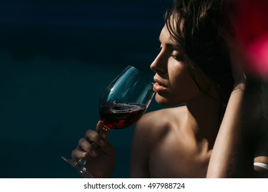 young sexy woman or girl with pretty face and long wet brunette hair drinking red wine from glass sunny day outdoor