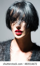 young sexy woman or girl with short brunette stylish hair and red lips on pretty face in black cloth on grey background, closeup