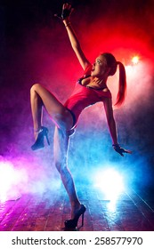 Young sexy woman go-go dancer in club. Red and blue lights with smoke effect.
