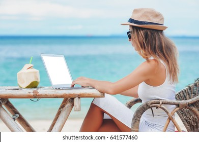 Young sexy woman with hat using laptop with empty white screen on the beach. Girl Freelancer working
