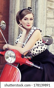 Young and sexy woman with her motor scooter - retro style image.