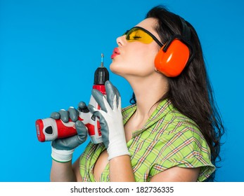 Young sexy woman holding a construction drill