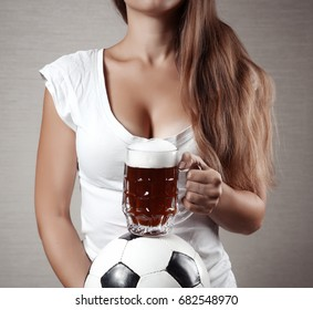 young sexy woman holding soccer ball and beer mug. Open breast. Closeup.
