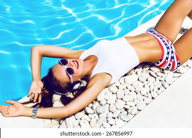 Young sexy woman laying and relaxed near pool at summer holiday nice hot day, wearing sexy mini shorts and crop top, listening and enjoy her favorite music at big headphones.