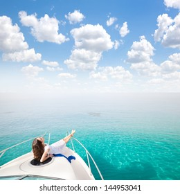 Young sexy woman lies in white dress enjoying clouds in the sky on yacht at the sea