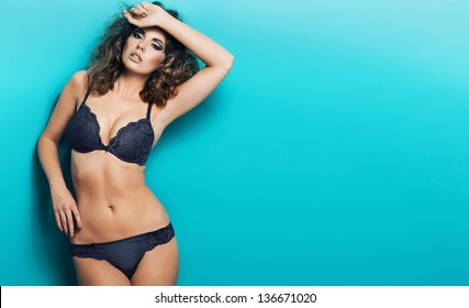 young sexy woman in lingerie posing on blue background