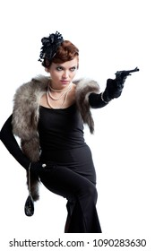 A young sexy woman in a long dress and a retro hat shoots a revolver in the victim, carved on a white background