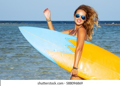 Young sexy woman with long hairs and sportive tanned body, smiling and jogging with surf board on the beach, ready for surfing. Waving hand. Wearing stylish sunglasses. Positive emotions. Close up