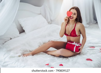 Young sexy woman is lying on bed in red lingerie with red heart in hand and smiling. Happy Saint Valentine's Day!