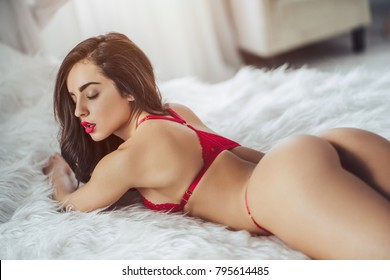 Young sexy woman is lying on white bed in red lingerie.