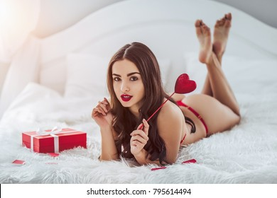 Young sexy woman is lying on bed in red lingerie with red heart in hand and gift box nearby. Happy Saint Valentine's Day!