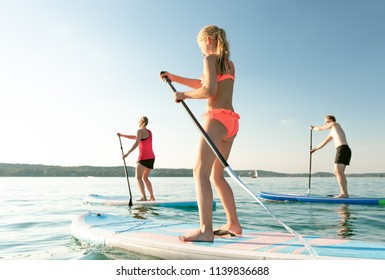 young sexy woman man girl are doing yoga on a stand up paddle board SUP on a beautiful lake sea water