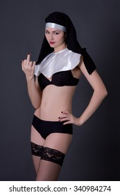 young sexy woman nun in lingerie showing middle finger over grey background