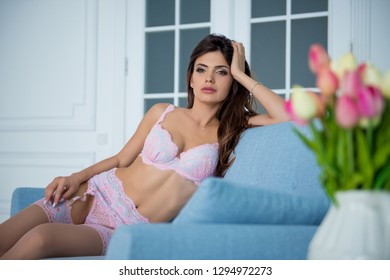 young and sexy woman in pink and white lingerie sitting on the couch. Spring mood and flowers