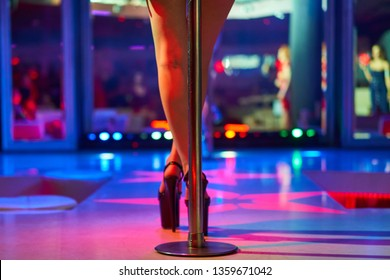 Young sexy woman pole dancing striptease with pylon in night club. Beautiful naked stripper girl on stage