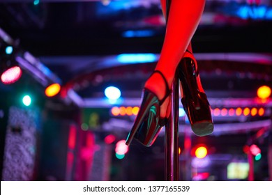 Young sexy woman pole dancing striptease with pylon in night club. Beautiful naked stripper girl on stage. club lights abstract background out of focus