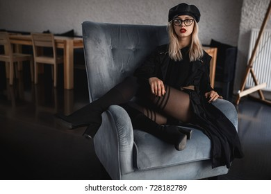 Young sexy woman in provocative pose sitting on the arm chair. Fashion and trendy clothes. Black leather cap, coat and shoes. Autumn style. Interior photo.