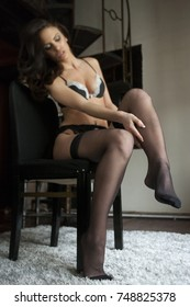 Young sexy woman putting on black stockings, natural film grain,natural light