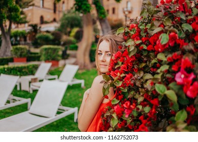 Young sexy woman with red bougainvillea flowers looking in the camera