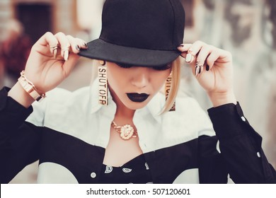 Young sexy woman with red lips, parted lips, wearing a red baseball cap sitting on a column in the style ,Sexy hip-hop woman in cap with long red hair. Fashion portrait of modern girl in cap