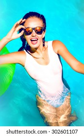 Young sexy woman relaxed at pool at summer nice hot day,wearing sexy full bikini,mirrored sunglasses,and laughing.Look at camera,sunbathing and playing with friends on the pool.Toned,lifestyle closeup