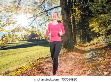 Young, sexy woman runs through a colorful autumn forest in the mountains - she is doing her running workout outdoor at a beautiful sundown and a amazing landscape