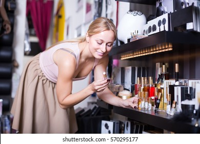 Young sexy woman selecting pheromones cologne in sex shop