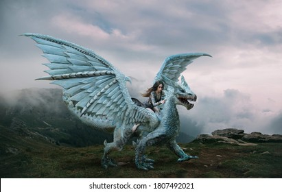 young sexy woman sits astride a wild  dragon. Fantasy photography. huge creature with spikes and wings stands on top of mountain. Beautiful nature dramatic sky white clouds blue fog. Girl elf warrior