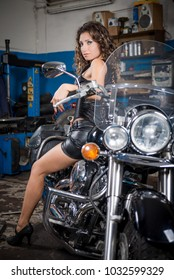 Young sexy woman sitting on motorcycle. Beautiful girl on a motorcycle. young biker girl. Girl in a black leather dress with curly hair on a bike. Garage with a motorcycle and a young sexy lady