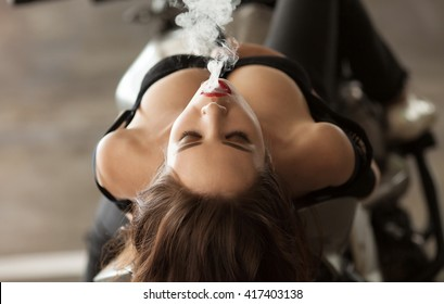 Young sexy woman sitting on motorcycle and smoking ( vaping ) e-cigarette.
