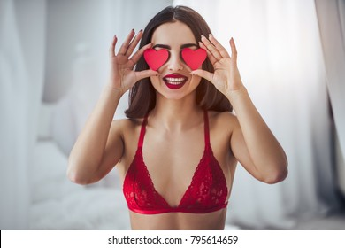 Young sexy woman is sitting on bed in red lingerie with red hearts in hands and smiling. Happy Saint Valentine's Day!