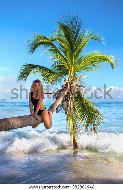 young sexy woman sitting on palm tree over blue sea