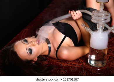 Young sexy woman  smoking the glassy  hookah on black background