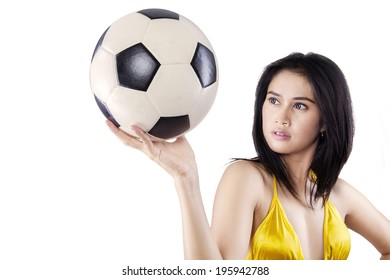 Young sexy woman with a soccer ball posing on white background