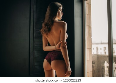 Young sexy woman is standing by the window topless in lilac panties. Back view.