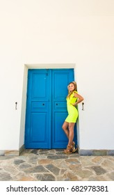 Young sexy woman standing next to blue door of building.